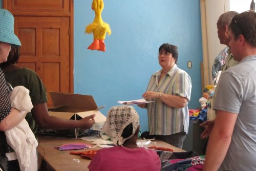 Diane explains to the group who traveled with her to Haiti about the vocational garment making program and training